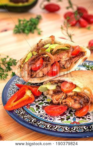 Stuffed Pita Bread With Fried Chicken With Onions, Lettuce Leaves, Cherry Tomatoes And Poured Sauce