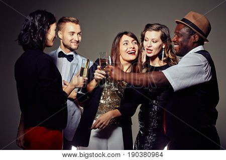 Group of well-dressed colleagues clinking champagne flutes together while having joyful office party, pretty woman whispering something in her friends ear