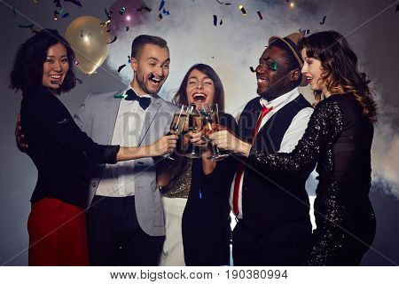 Joyful young friends toasting with champagne flutes and wishing happy New Year to each other while gathered together in night club