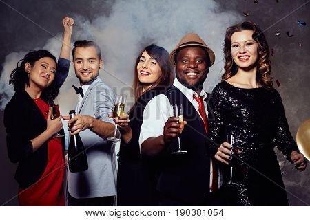 Cheerful young people enjoying each others company in night club, they holding champagne flutes in hands and looking at camera with toothy smiles