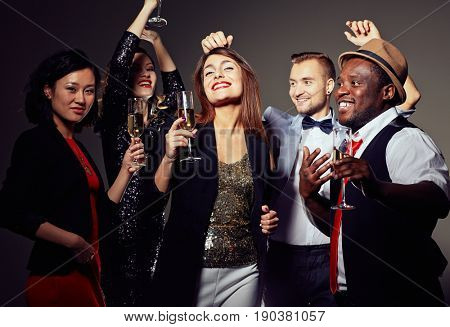 Multi-ethnic group of smiling friends in evening wear posing for photography while dancing with champagne flutes in hands
