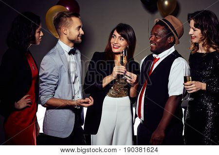 Handsome young man entertaining his colleagues with small talk while having office party, two beautiful women holding champagne flutes in hands