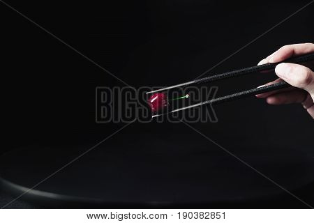 Hand holding black chopsticks with a red cherry on a black background.