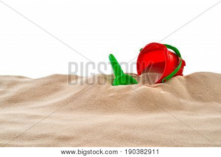 On the Beach - Sand dune with sand toys in front of a white background - clipping path included