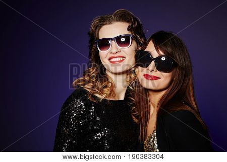 Waist-up portrait of two stylish women in sunglasses looking at camera with wide smiles while standing against dark background, studio shot