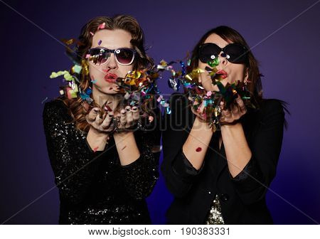 Trendy young women in sunglasses blowing colorful confetti while standing against dark background, waist-up group portrait