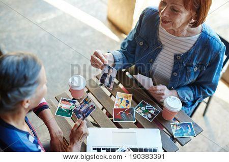 Two senior buddies looking through photos of their relatives