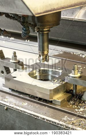 Square industrial metal mold/blank milling. Metalworking mechanical engineering lathe milling and drilling technology. Indoors vertical image.
