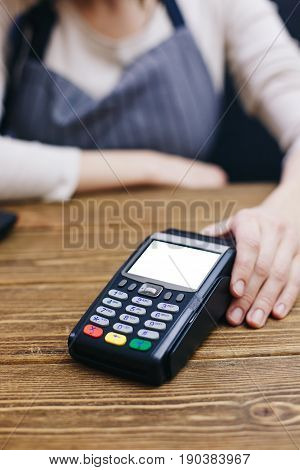 Crop woman in apron outstretching POS machine on wooden counter.
