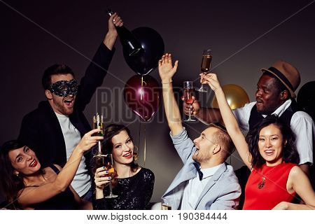 Having birthday party at home: cheerful friends looking at camera with toothy smiles while clinking champagne flutes together, colorful balloons on background