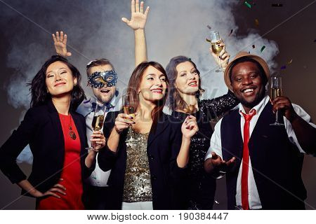 Enthusiastic stylish friends hanging out in trendy night club, they holding champagne flutes in hands, young bearded man in carnival mask dancing with hands up