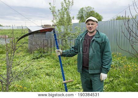 man mows the grass using a scythe