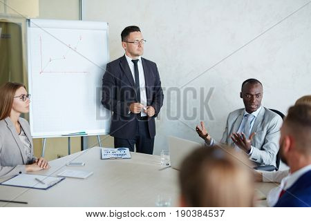 Middle-aged bearded tutor holding career development course for business people, they gathered together in modern meeting room