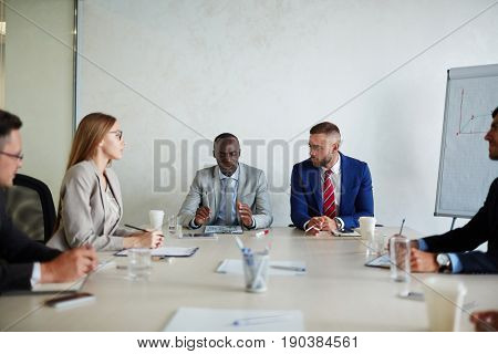 Colleagues attending work meeting: they gathered around table and listening to their Afro-American boss with concentration