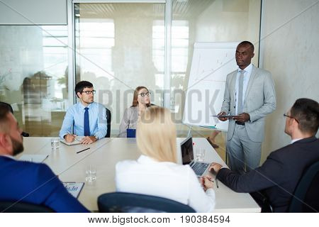 Portrait of handsome Afro-American manager standing at marker board and presenting his ideas to coworkers in modern meeting room