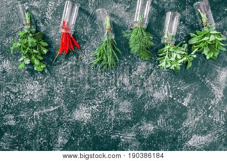Fresh cilantro, tarragon, dill, oregano, chili peppers and lemon balm in spice jars over dark grey spotty background. Top view