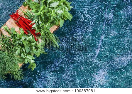 Fresh chili peppers, cilantro, dill, thyme, lemon balm, tarragon and oregano  potherbs on cutting board ready for cooking. Dark blue spotty background. Top view