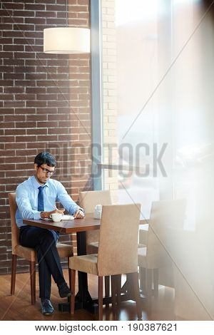 Bearded white collar worker in eyeglasses working on his project while sitting in spacious coffeehouse with panoramic windows