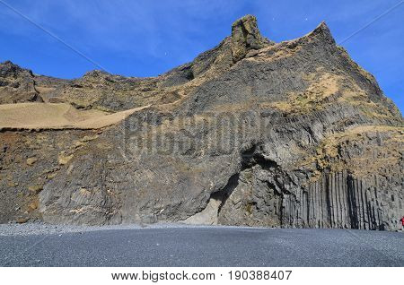 Iceland's basalt column rock formations on black sand beach.