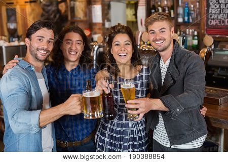 Portrait of happy friends tossing beer glasses and bottles in pub