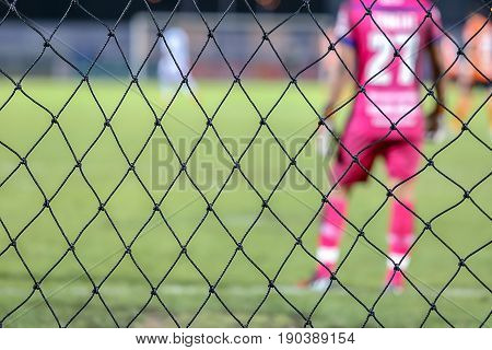 net with blurry goalkeeper at football or soccer stadium field.
