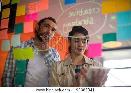 Female executive using digital tablet while male executive looking at sticky notes in office
