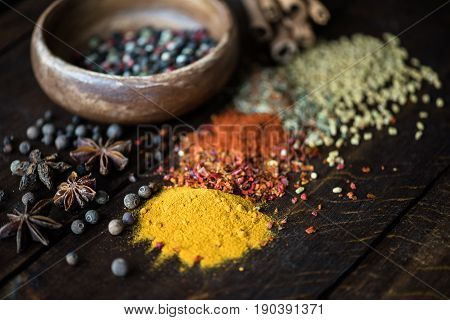 Different Kinds Of Pepper In Bowl And Spices With Herbs Scattered On Wooden Tabletop