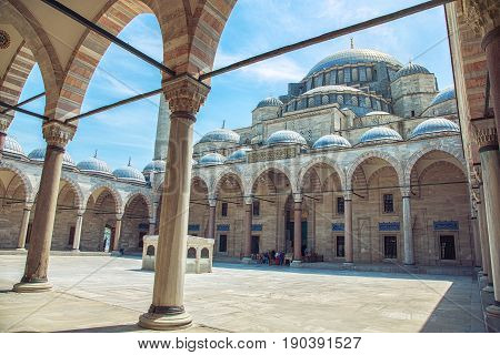 Exterior view of Suleymaniye Mosque through arches in its courtyard in Istanbul Turkey. The mosque was constructed by Sinan for sultan Suleyman the Magnificent