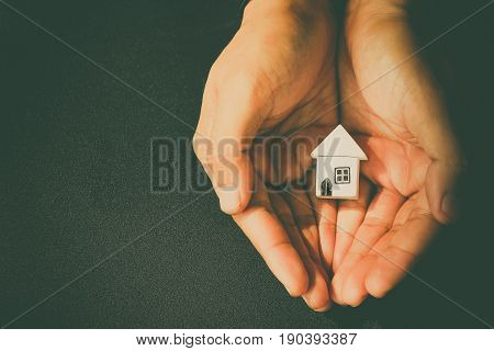 Close up woman hands holding house model eco concept