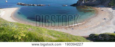 people enjoying a hot summer day on a beautiful hidden beach on the Jurassic Coast of Dorset, UK - British summer holiday destination