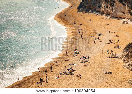 people enjoying a hot summer day on a beautiful hidden beach on the Jurassic Coast of Dorset, UK - Britiish summer holiday destination
