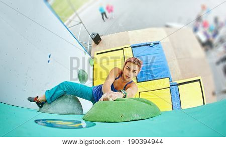 woman climber climbs a bouldering problem on climbing gym. woman makes hard wide move on the top and wins. Climbing competition