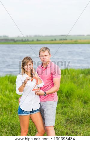 Man and woman holding the number 2 in nature. Concept of numbers, measurement, amount, quantity, accounting and mathematics.