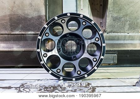 Round car alloy black new rim die mounting in milling and lathe cnc machine. Front view of working process. Mechanical engineering and metalworking industry. Horizontal indoors image.