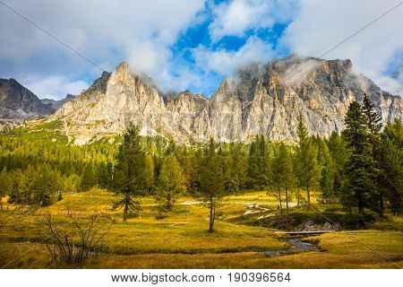 The concept of ecological and extreme tourism. The dizzying Dolomites. Sharp rocks surround the grassy valleys. A cold fast spring flows through the valley