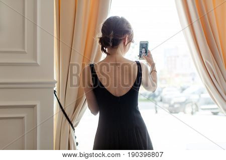 Woman blogger doing selfie at the window. Anonymous woman in elegant black dress standing near window in banquet hall.