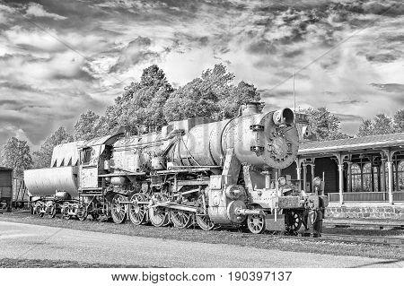 Surrealistic monochrome old steam locomotive on station platform. Dramatic cloudy sky background.