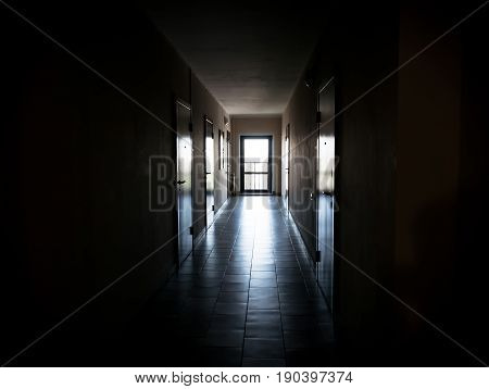 Long dark corridor with doors to the apartments gave the tunnel the light. an apartment building or Dorm black background.