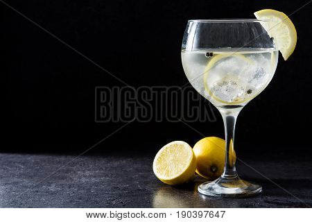 Glass of gin tonic with lemon on black stone background