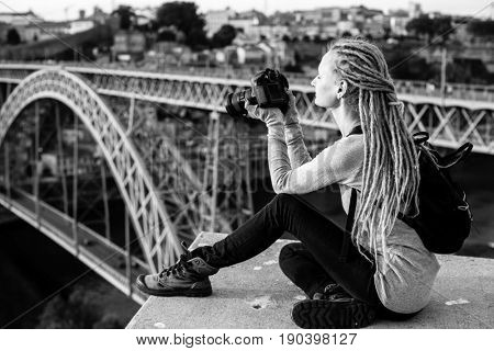 Young beautiful woman with dreadlocks and a camera sits taking pictures of a Dom Luis I bridge  in old Porto, Portugal. Tourism and travel, black and white photo.