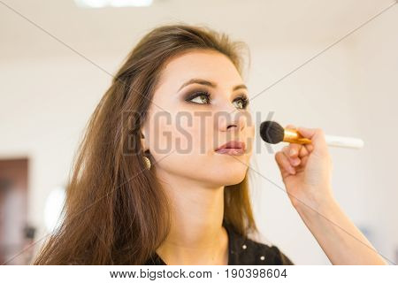 make-up artist doing make-up beautiful girl in the salon, beauty concept and style.