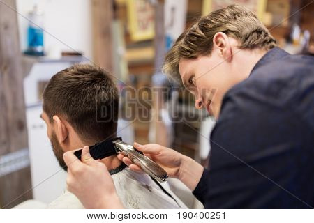 grooming, hairstyle and people concept - man and barber or hairdresser with trimmer and comb cutting hair at barbershop
