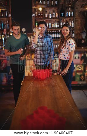 Group of happy friends playing beer pong game in pub