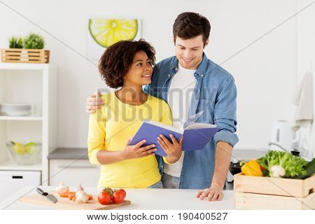 people, cooking food and healthy eating concept - happy couple with cookbook and vegetables at home kitchen