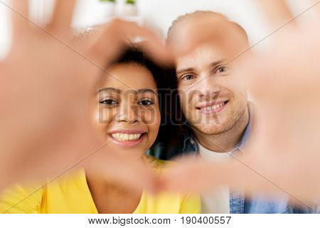 valentines day, love and people concept - happy multiethnic couple looking through heart shape made of fingers