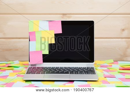 Colorful blank sticky notes stuck to a laptop screen and scattered on the surrounding desk conceptual of reminders multitasking and business schedule