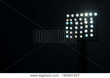 Spotlight of football stadium at night with dark background.
