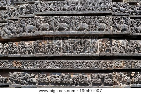 Patterns of the Hindu temple walls with friezes that consist of elephants, lions, scrolls, horses, vedic and puranic scenes, mythical beasts and swans. 12th century Hoysaleshwara temple in Halebidu, India