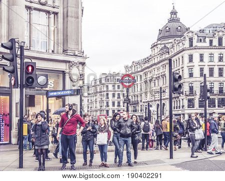 London, UK - March 19, 2017: London leaving the Oxford Circus Station in London. People stand at the traffic lights at Oxford Street on a cloudy day in March