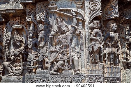 Ancient soldier with bow and arrow on the Hindu temple walls with friezes that consist of patterns, vedic and puranic scenes, mythical beasts and gods. 12th century Hoysaleshwara temple in Halebidu, India